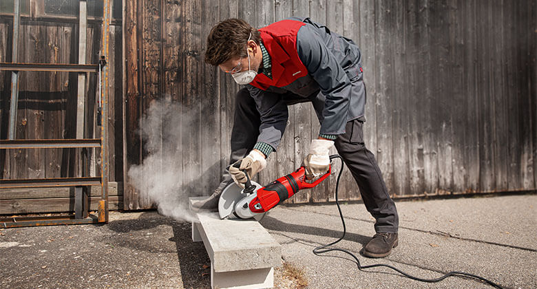 man cuts with Einhell angle grinder through concrete
