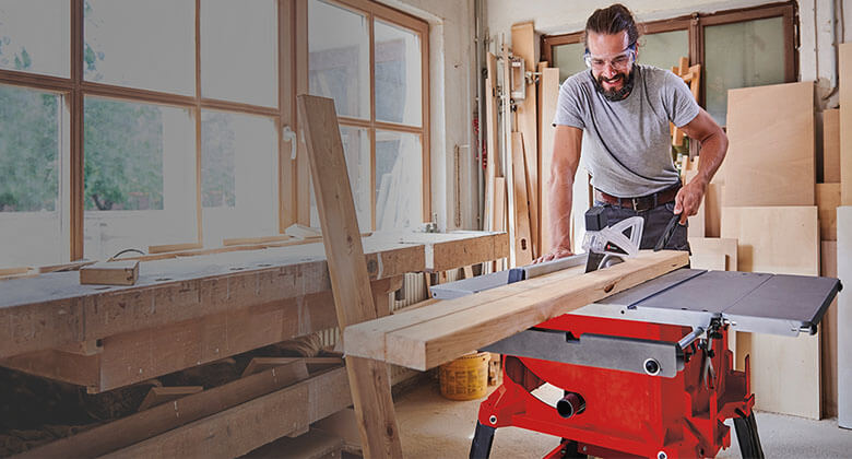 man cuts wood with circular table saw from Einhell